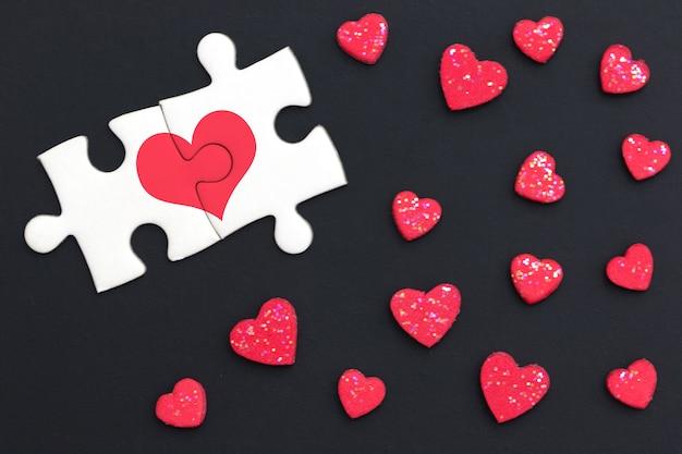 Dos rompecabezas pintaron un corazón rojo y continuaron sobre un fondo negro con muchos corazones rojos.