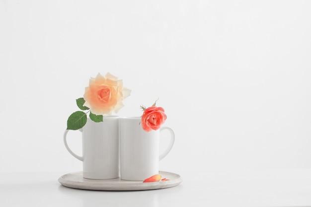 Dos rosas en tazas sobre fondo blanco.