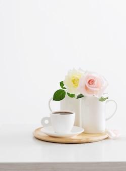 Dos rosas en tazas con taza de café