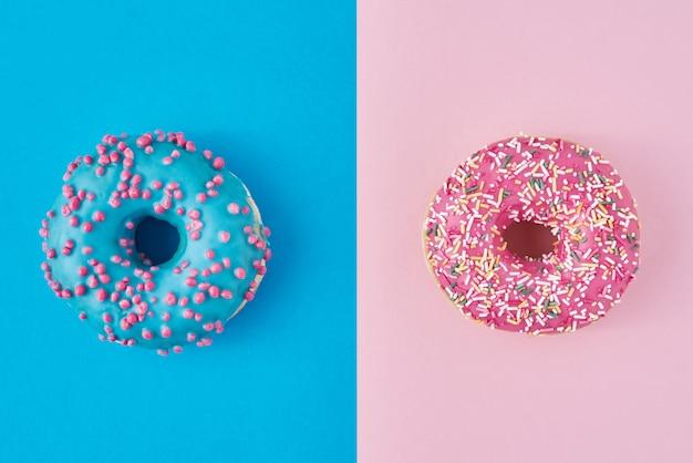 Dos rosquillas en rosa pastel y azul. minimalismo composición creativa de alimentos. estilo plano laico