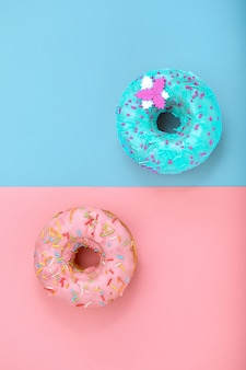 Dos rosquillas en rosa pastel y azul superficie. minimalismo composición creativa de alimentos. estilo plano laico