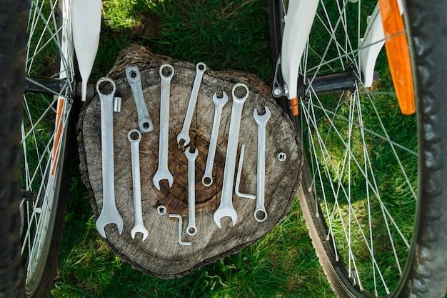 Dos ruedas de bicicleta y herramientas de reparación con fondo verde exterior, vista posterior.