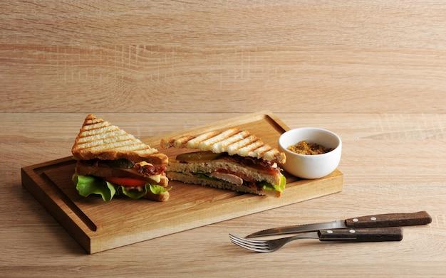 Dos sandwich triangular con tocino y pechuga de pollo sobre una tabla de madera