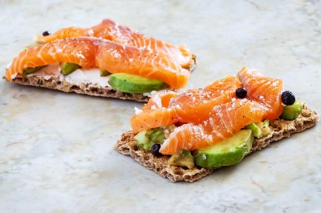 Dos sándwiches crujientes con aguacate y salmón ahumado.