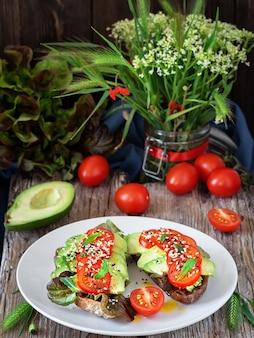 Dos sándwiches con pan recién horneado, aceite de oliva, lechuga, aguacate, semillas de sésamo y tomates cherry en una placa blanca.