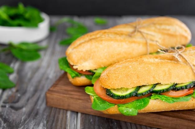 Dos sándwiches con rodajas de espinacas y pepino.