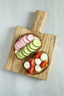 Dos sándwiches vegetarianos en rebanadas de pan oscuro con verduras rábano, pepino, tomates cherry sobre una tabla de cortar de madera. composición central sobre un fondo de madera blanco plano, vista superior.