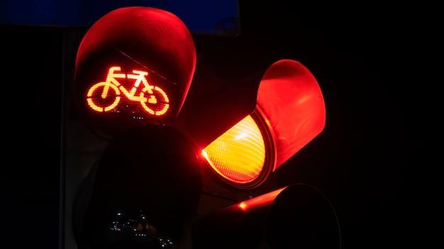 Dos semáforos rojos con logotipo de bicicleta en uno por la noche en bucarest, rumania