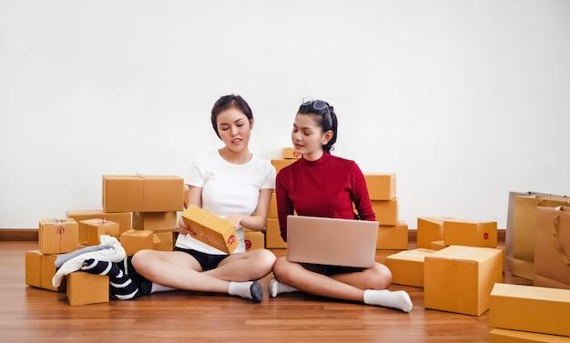 Dos señoras que venden en línea en la oficina en casa, negocios asociados, trabajando juntos
