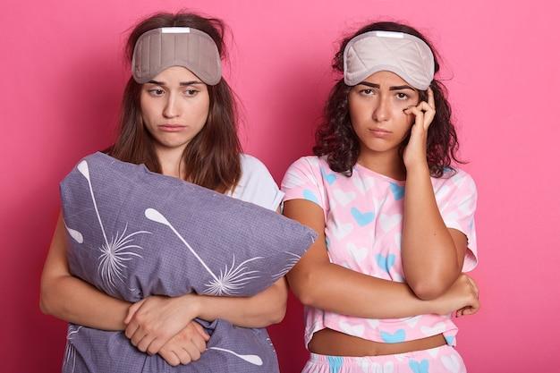 Dos señoras soñolientas de pelo oscuro con antifaz para dormir en la frente
