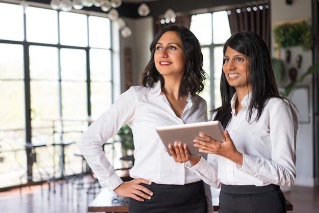 Dos señoras sonrientes del negocio usando la tableta en café.