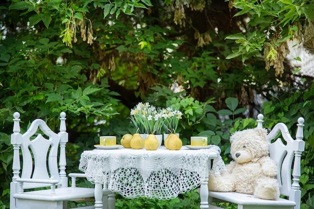 Dos sillas de madera y una mesa en el patio con flores y equipos de té.