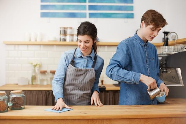 Dos simpáticos baristas trabajando en el mostrador del bar, felices.