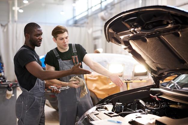Dos simpáticos mecánicos de automóviles profesionales durante el trabajo