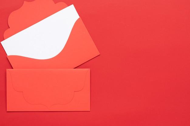 Dos sobres de saludo rojos sobre un fondo rojo y uno de los sobres contiene un membrete blanco vacío para el texto