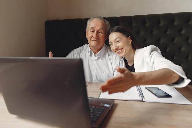 Dos socios comerciales que trabajan con una computadora portátil en un café