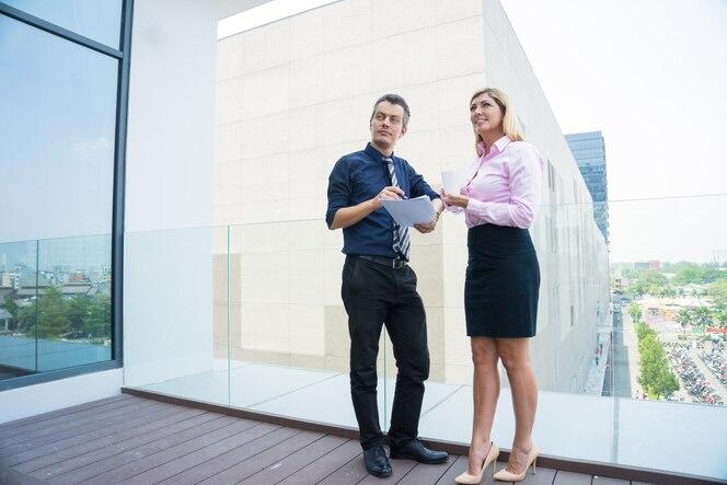 Dos socios comerciales sonrientes que miran la construcción al aire libre.