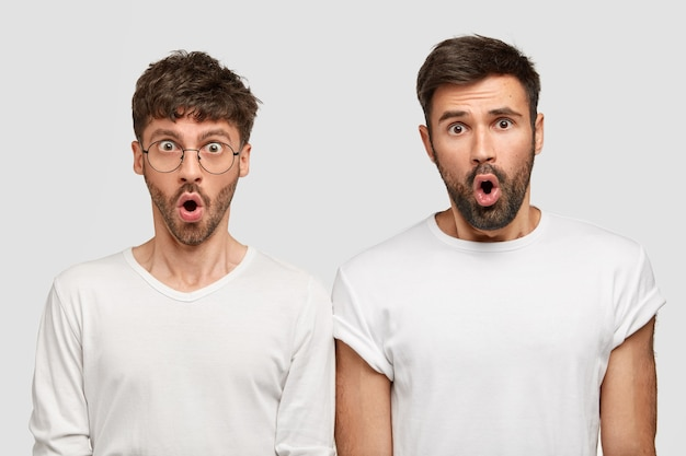 Dos socios de hombre joven barbudo tienen expresiones de asombro, expresan asombro e incredulidad