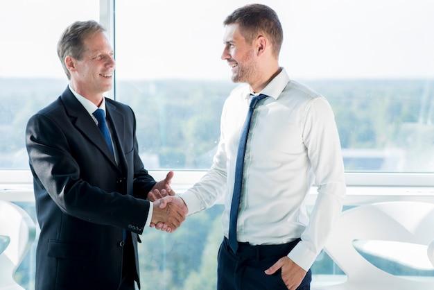 Dos socios de negocios feliz dándose la mano en la oficina