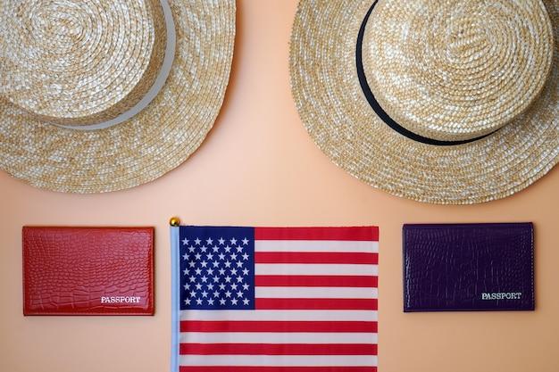 Dos sombreros de paja de playa para mujeres, pasaportes y la bandera estadounidense sobre un fondo beige.