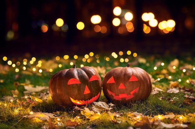 Dos sonrientes calabazas de halloween en un césped con luces en un parque por la noche