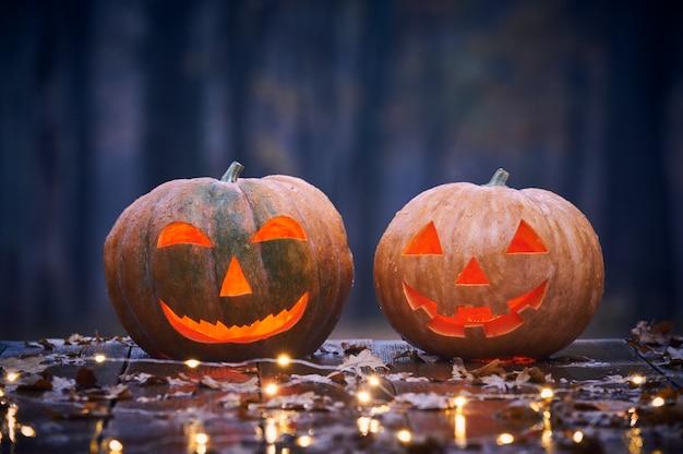 Dos sonrientes calabazas de halloween en una mesa de madera con luces en un bosque místico en la noche