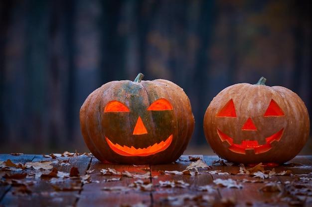 Dos sonrientes calabazas de halloween en una tabla de madera en un bosque místico en la noche