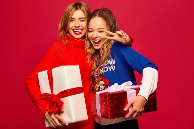 Dos sonrientes hermosas mujeres en elegantes suéteres con grandes cajas de regalo