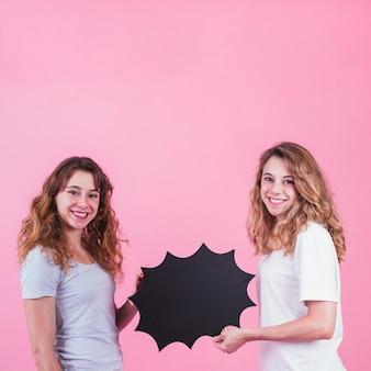 Dos sonrientes jóvenes amigas sosteniendo el bocadillo de diálogo en blanco sobre fondo rosa