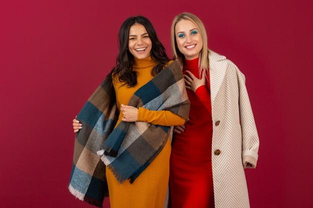 Dos sonrientes mujeres elegantes atractivas en vestido de moda otoño invierno y abrigo posando aislado en la pared roja