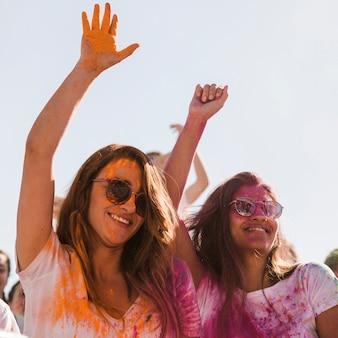 Dos sonrientes mujeres jóvenes con color holi en su cara bailando juntas