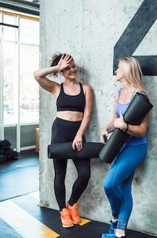 Dos sonrientes mujeres jóvenes con estera de ejercicio en el gimnasio