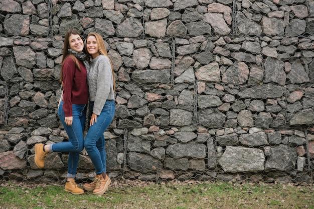 Dos sonrientes mujeres jóvenes frente a muro de piedra