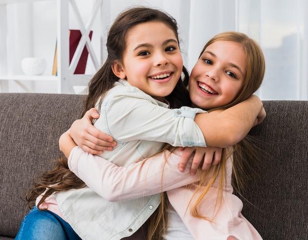 Dos sonrientes niña abrazándose mirando a cámara en casa
