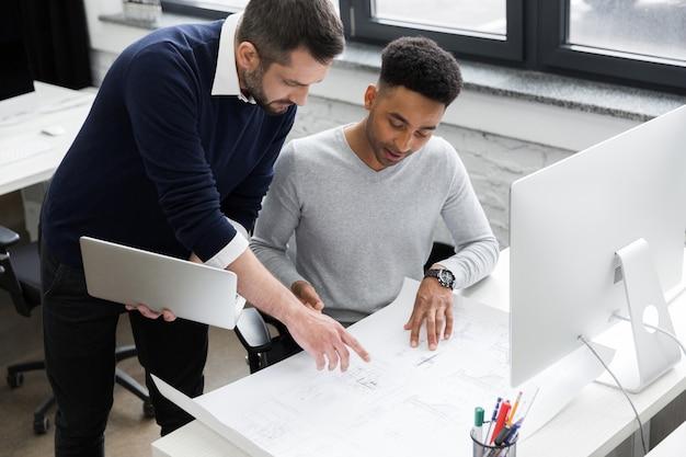 Dos sonrientes oficinistas hombres trabajando con laptop