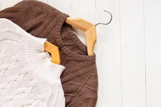 Dos suéteres de punto en perchas sobre fondo blanco de madera vista superior endecha plana.