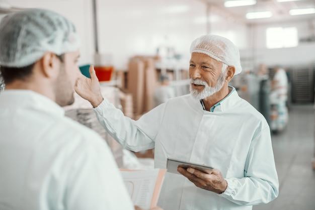 Dos supervisores discutiendo sobre la calidad de los alimentos en la planta de alimentos. el más joven tiene una carpeta con datos mientras que el más viejo tiene una tableta.