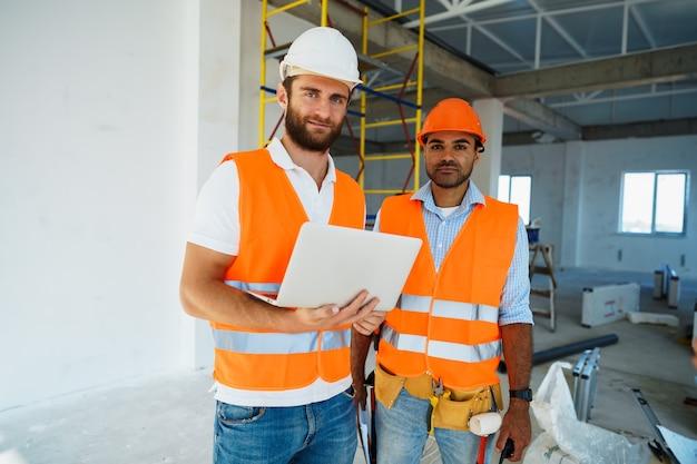 Dos supervisores especialistas en cascos con laptop en el sitio de construcción para trabajar