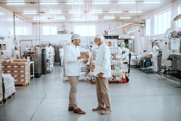 Dos supervisores hablando sobre la calidad de la comida. una tableta de explotación más joven mientras que una carpeta de explotación mayor con gráficos. ambos visten uniformes esterilizados y redecillas para el cabello. interior de la planta de alimentos.