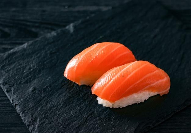 Dos sushi con salmón en piedra