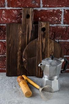 Dos tablas de cortar de madera y utensilios de cocina. olla de moka