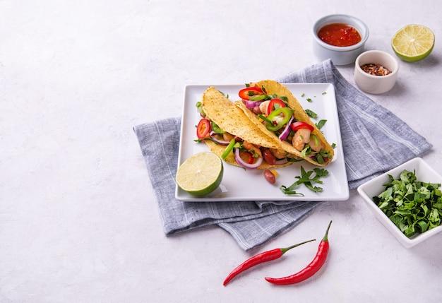 Dos tacos callejeros mexicanos con pollo, cebolla, chiles, maíz y frijoles en un plato para servir con limón y especias. espacio plano laico y copia