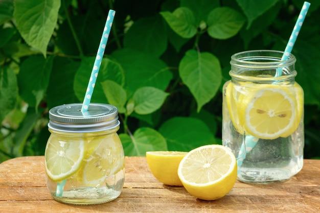 Dos tarros de limonada se colocan en un soporte de madera.