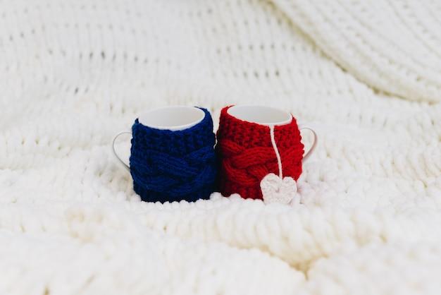Dos tazas, azules y rojas, aisladas en una manta para el día de san valentín