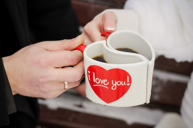 Dos tazas blancas en forma de corazones en las manos de los novios. san valentín, el día del amor y el matrimonio.