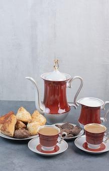 Dos tazas de café aromático con pasteles en mesa gris.