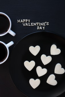 Dos tazas de café y bombones con forma de corazón blanco - inscripción happy valentine