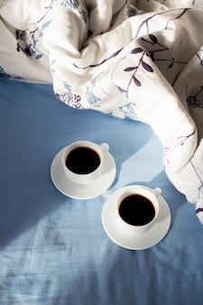 Dos tazas de café en la cama, la luz del sol.