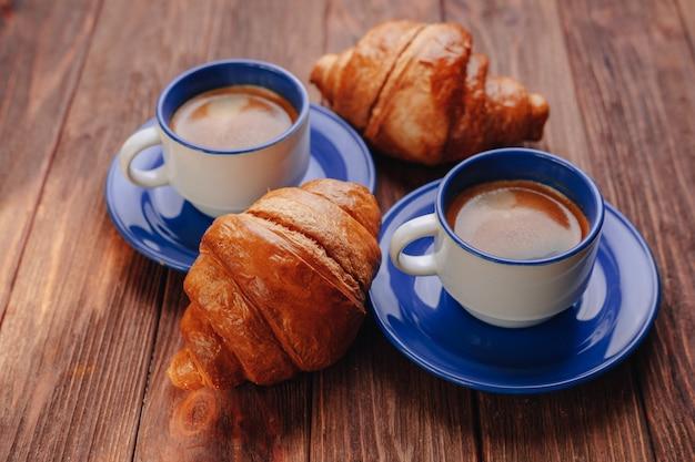 Dos tazas de café y croissants sobre un fondo de madera