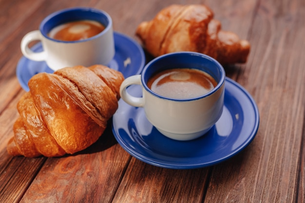 Dos tazas de café y croissants.